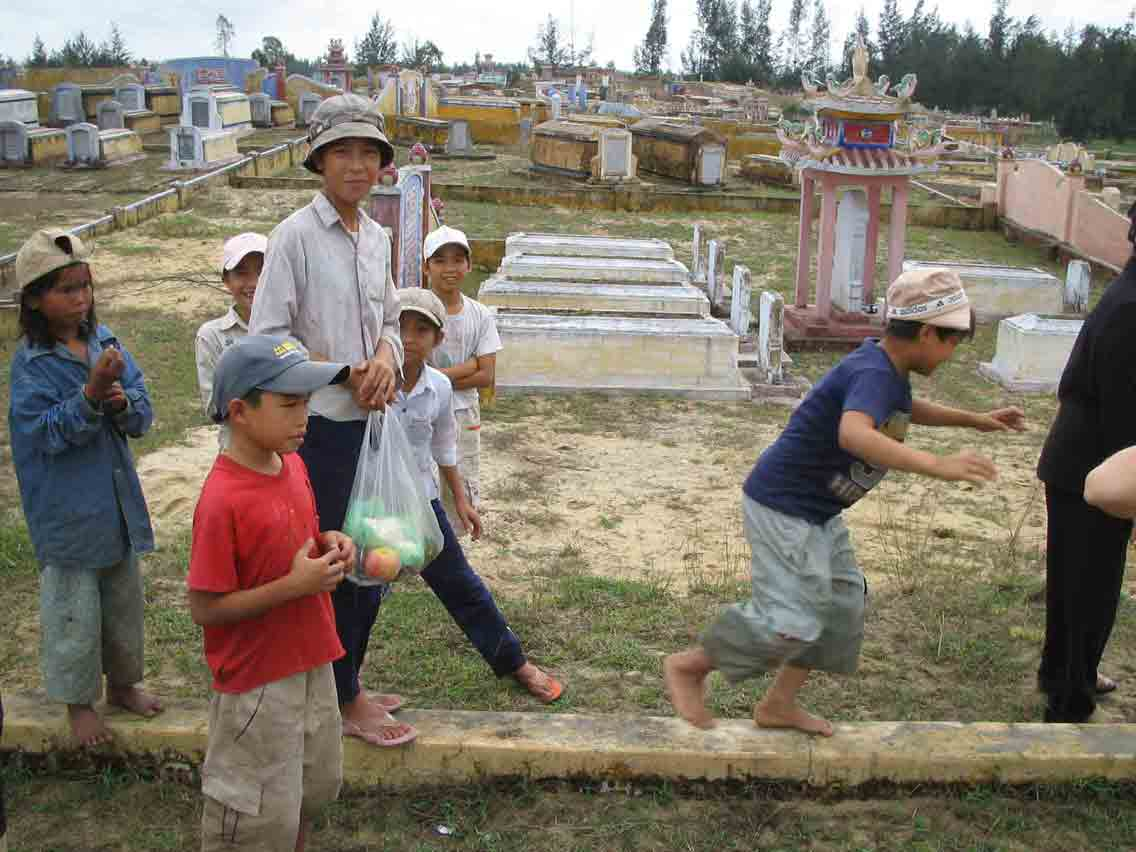 Grave-robbing kids outside central Da Nang, Vietnam (The kids extort families who come to visit relatives.)